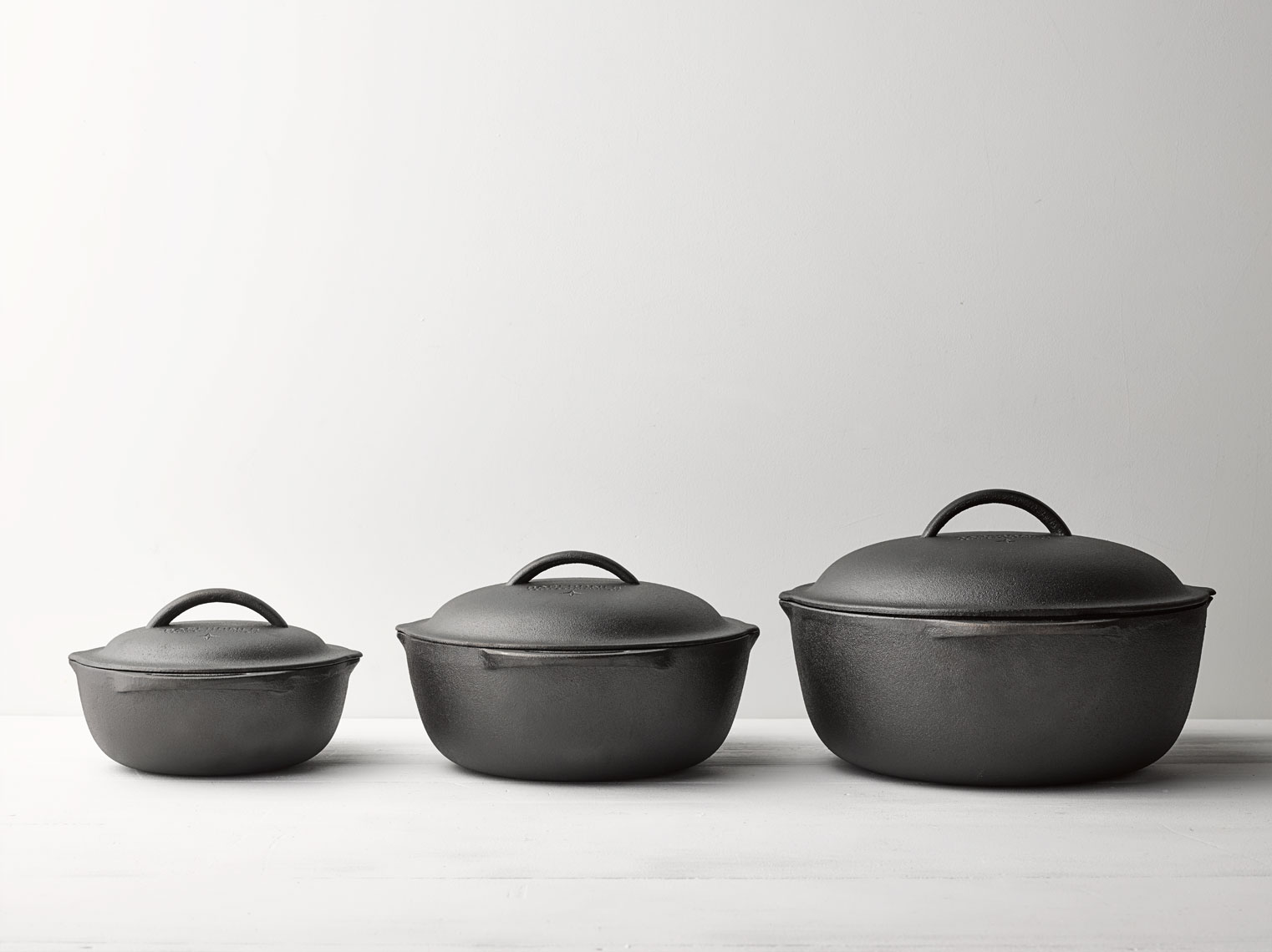 Cast iron pots in a straight line with soft shadows