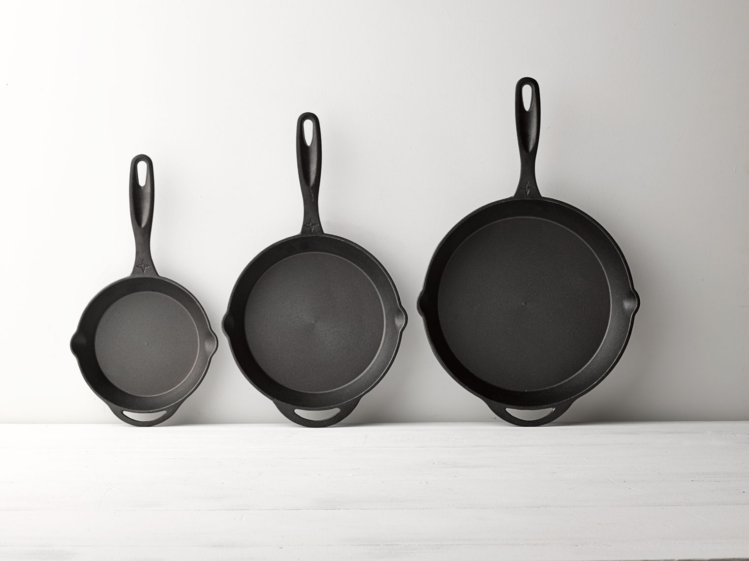 cast iron pan set in three sizes on a wall and table