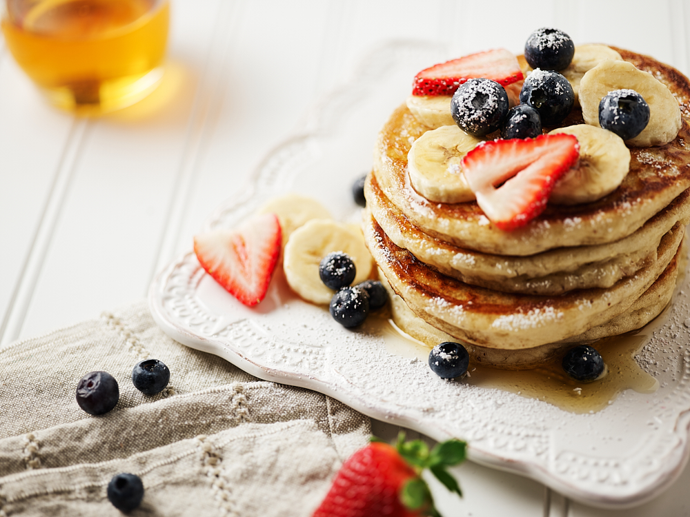 Gluten free pancakes on a plate with fresh fruit and syrup