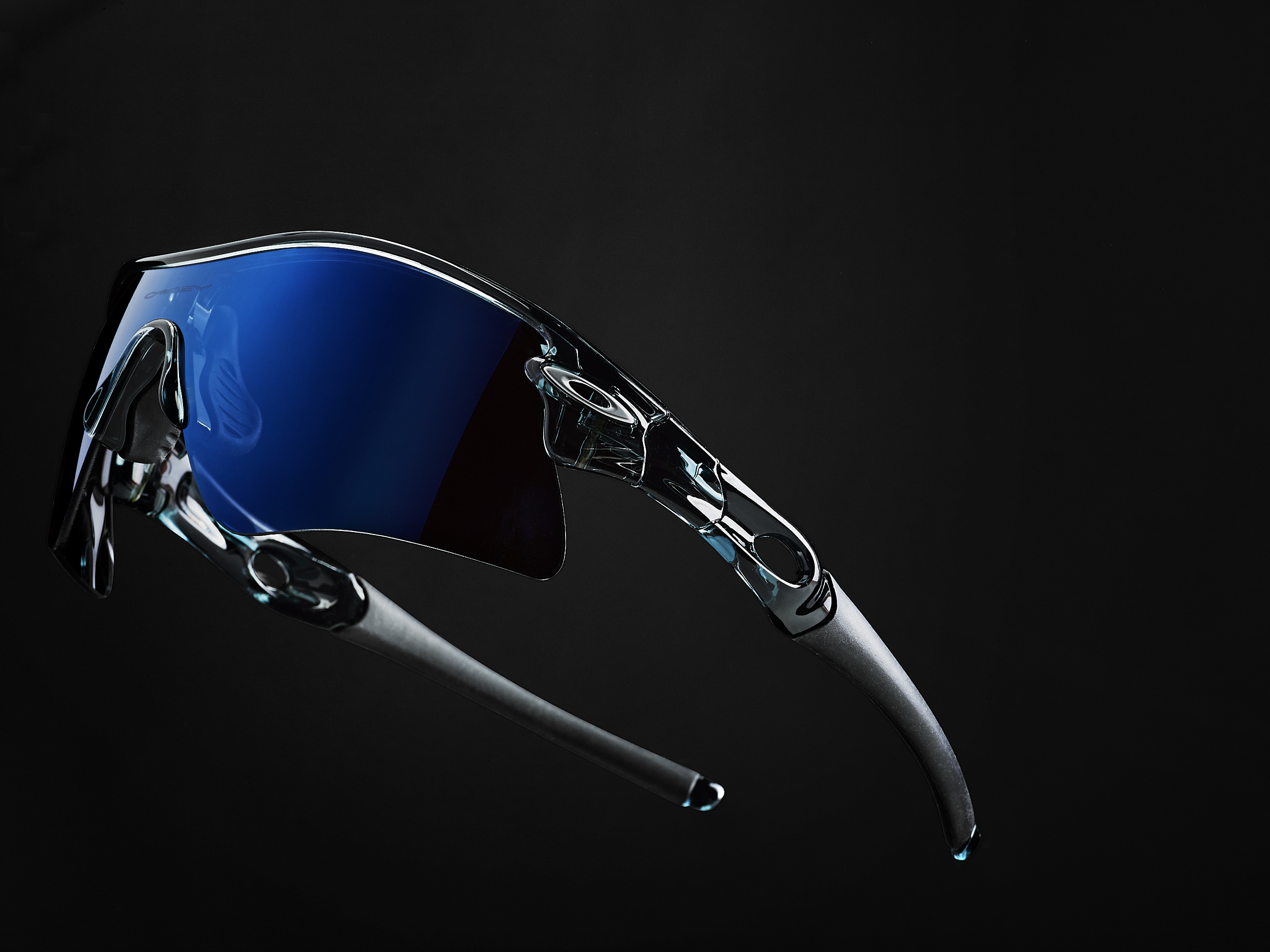 Still life shot of blue Oakley sunglasses on a black background fading dramatically Studio lighting