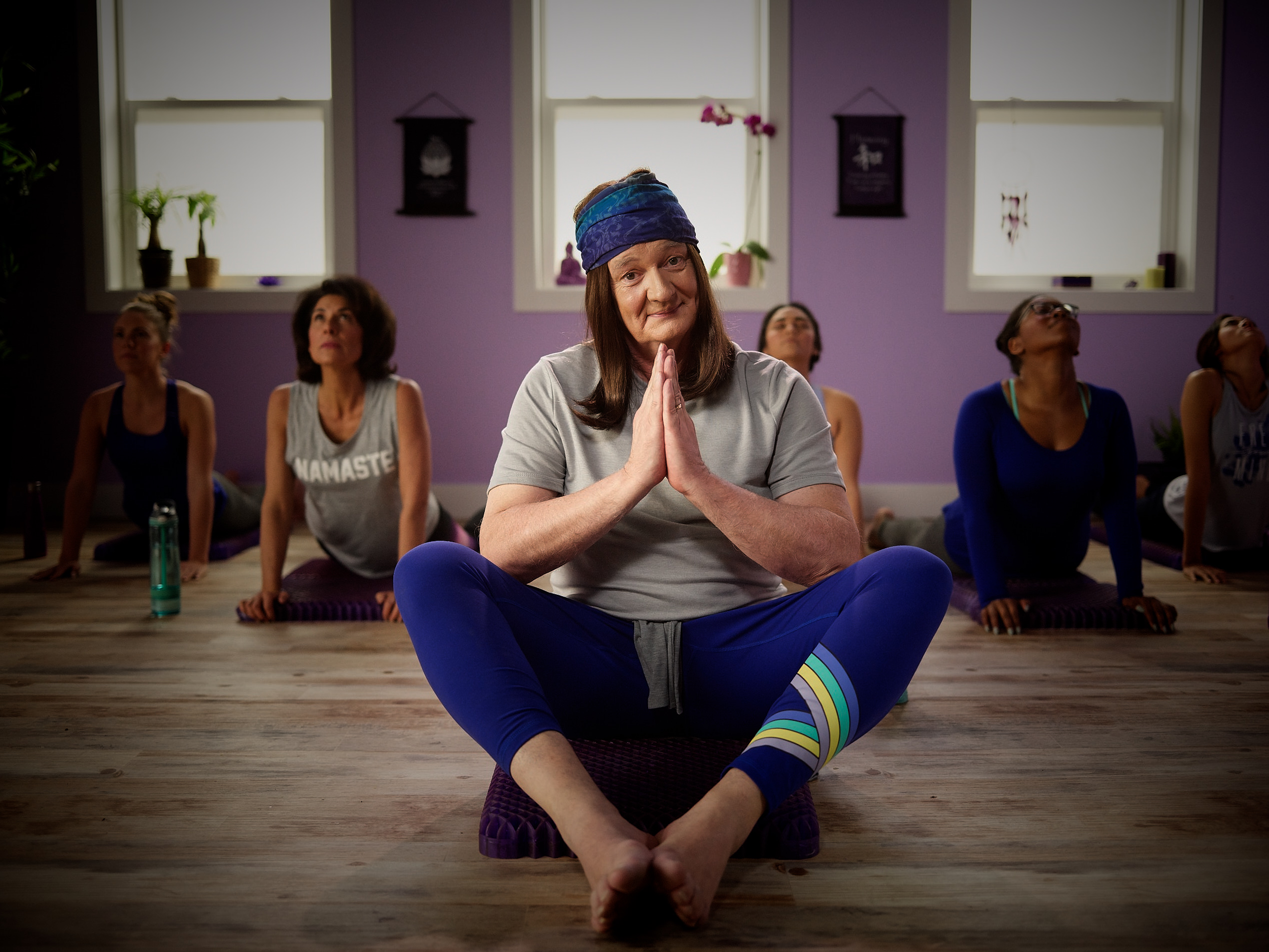 COLIN MOCHRIE AS A YOGIE DOING YOGA ON A PURPLE SEAT CUSHION