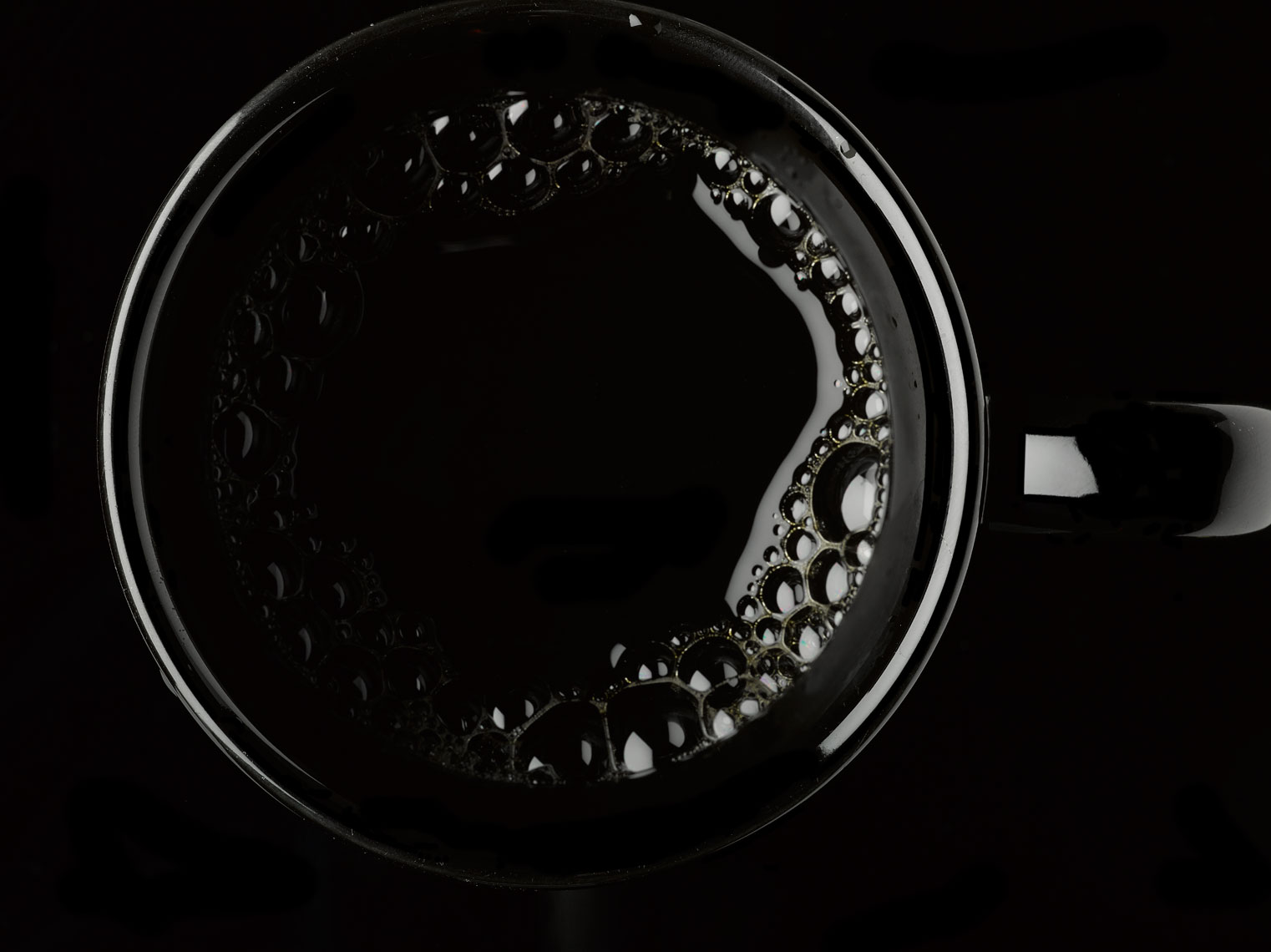 Coffee in a black cup from above on a black background