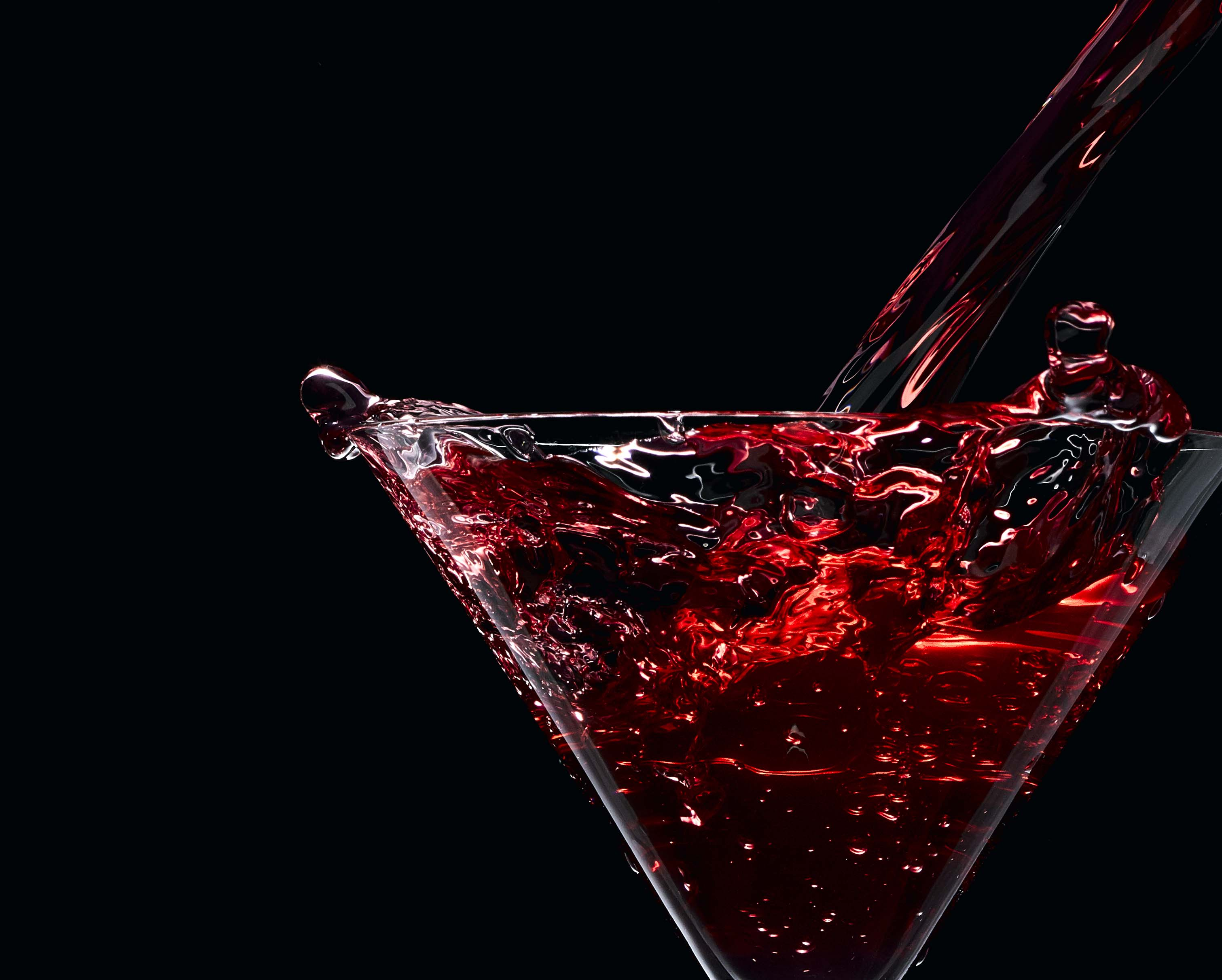 Mix red alcohol drink pouring into glass with a splash and black background